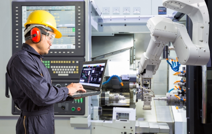 Custom Metal Design worker using a robotic arm